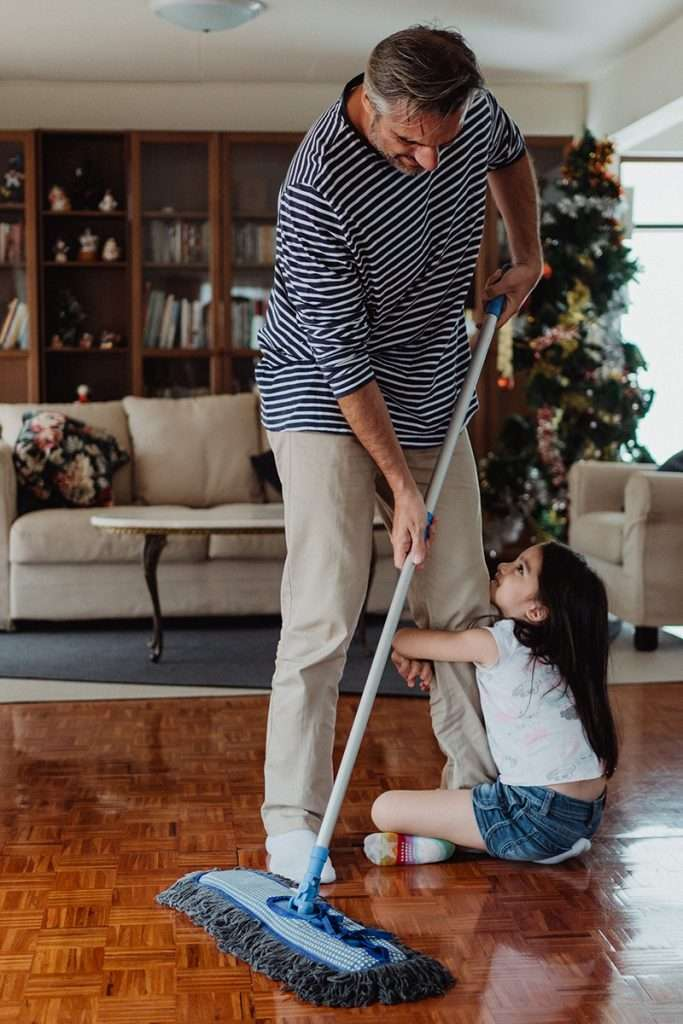 Little girl holding onto a man's leg as he uses a non toxic floor cleaner