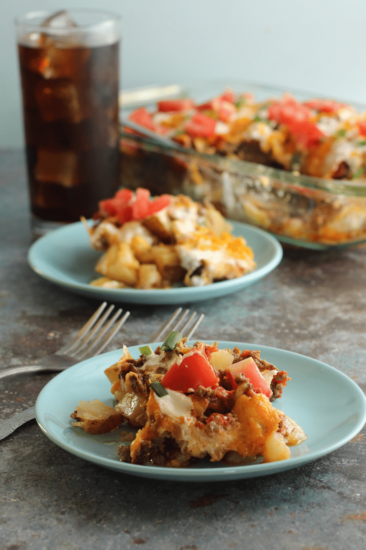 taco potato bake on blue plates with forks and drink in back