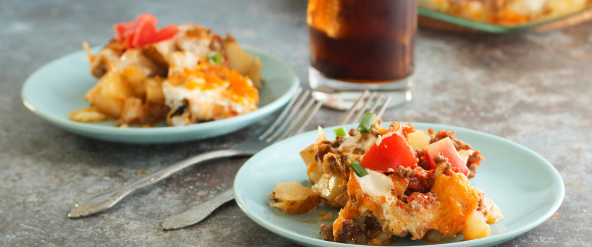 taco potato bake on blue plates with forks and drink