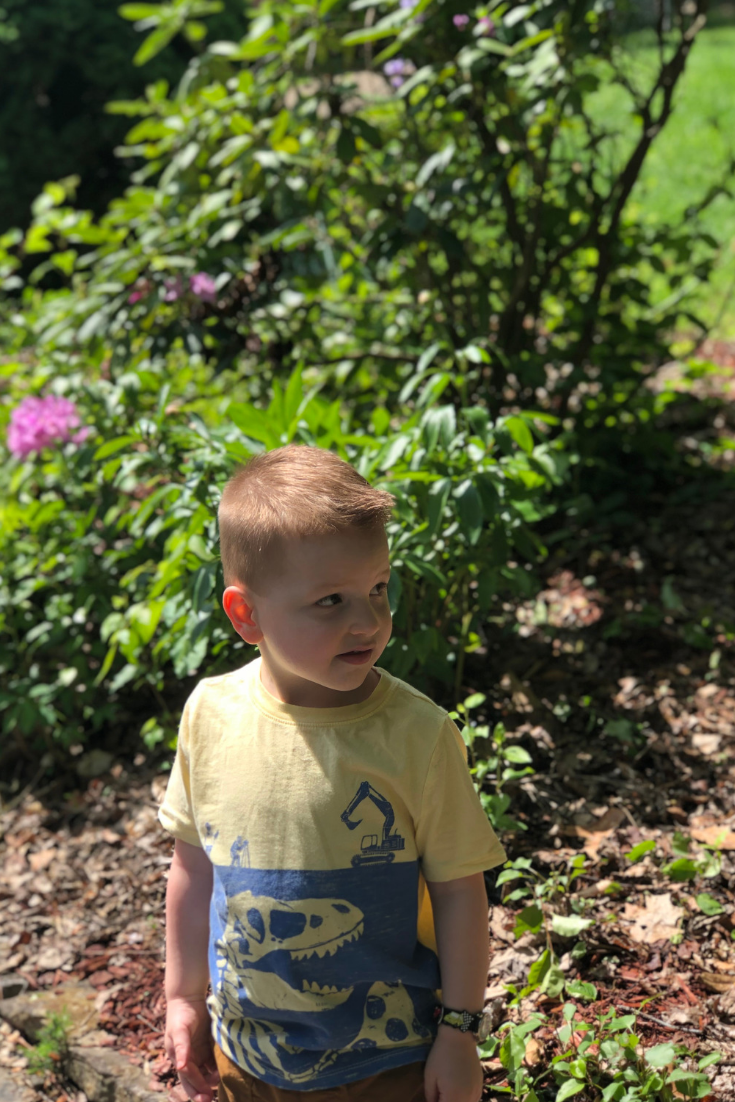 child outside standing by bushes