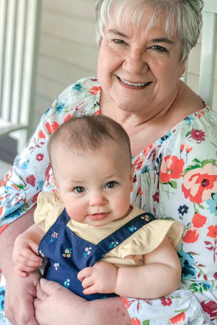 grandma holding baby and smiling
