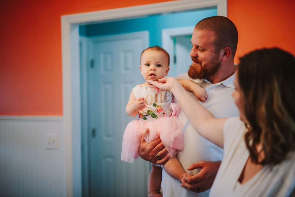 Mom and dad holding baby girl in first birthday outfit tutu
