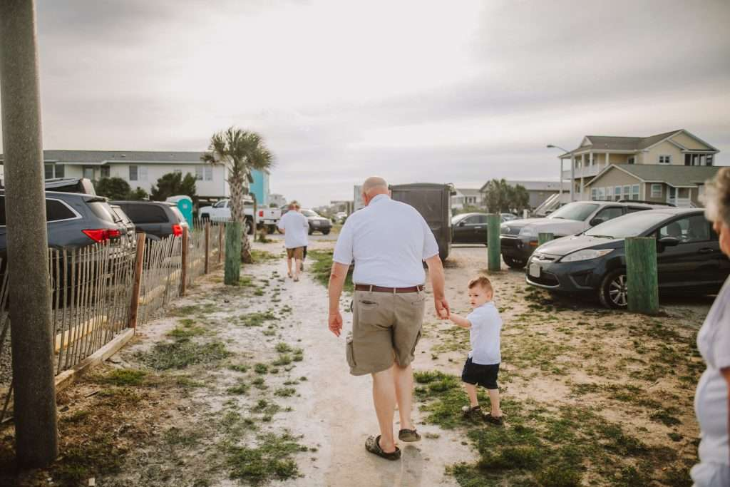 Toddler and grandpa walking to beach in matching shirts