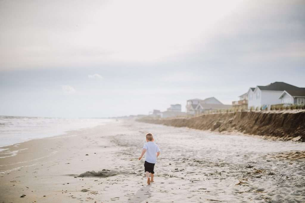 Toddler boy running down beach in white shirt and jean shorts