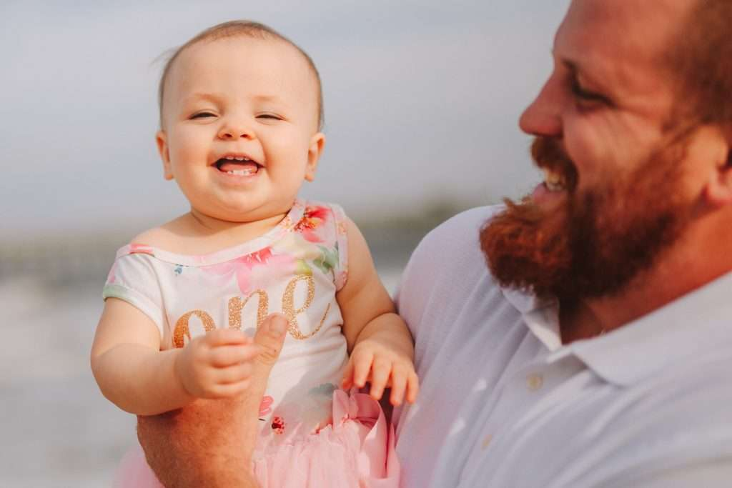 One year old laughing on beach at cake smash session