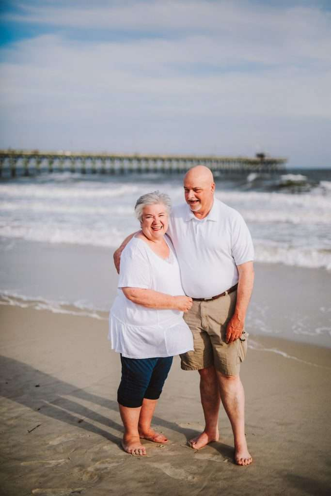 Grandparents laughing at photo session on beach in matching white shirts