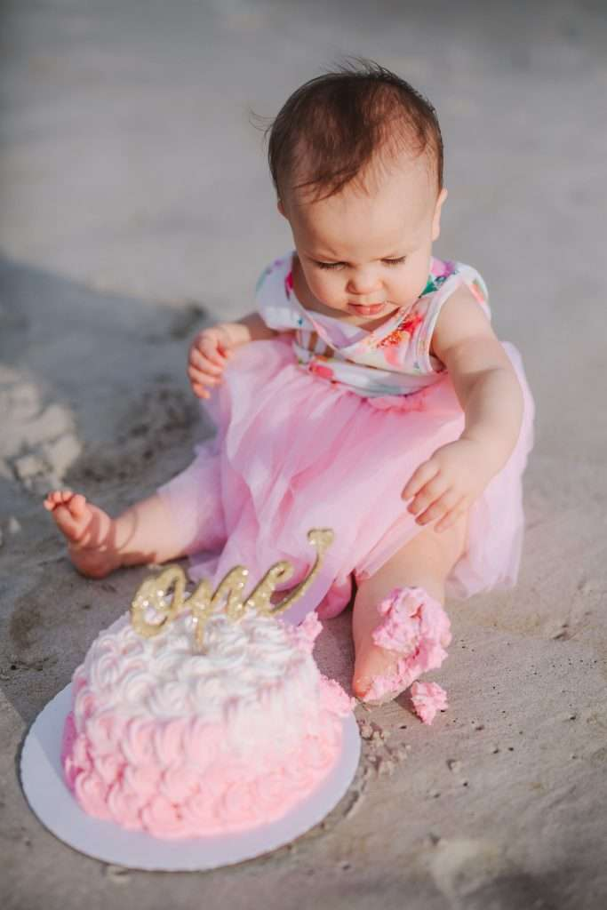 One year old with pink rosette cake and gold cake topper on beach