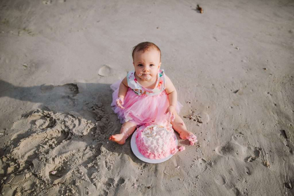 One year old in pink tutu with pink rosette cake on beach
