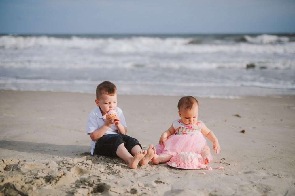 Toddler big brother and one year old on beach for cake smash session