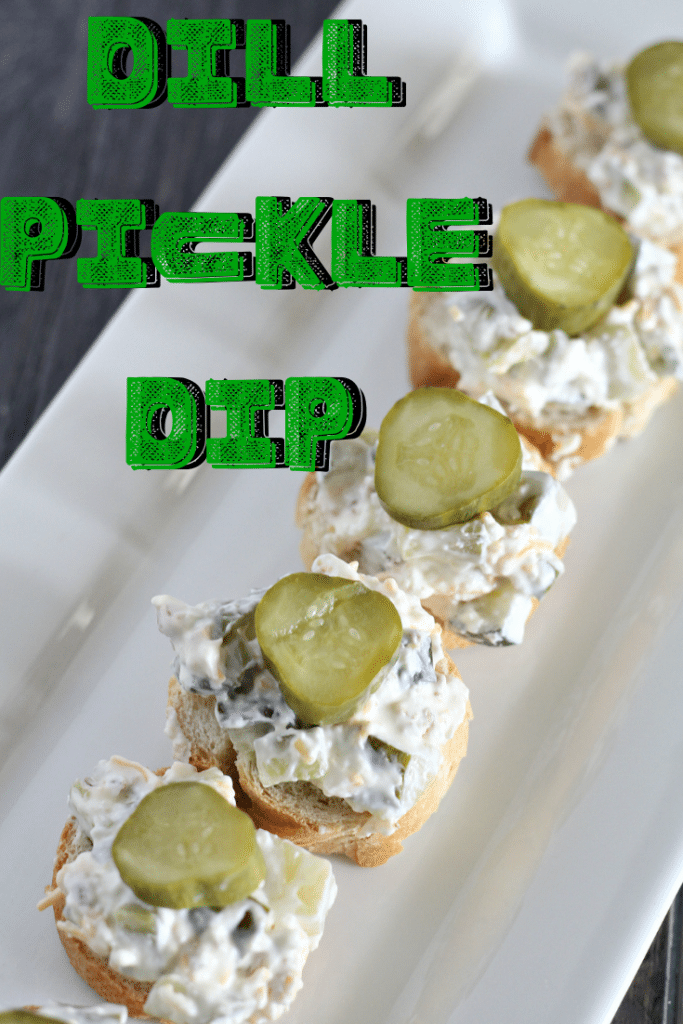dill pickle dip on bread slices, served on a white plate