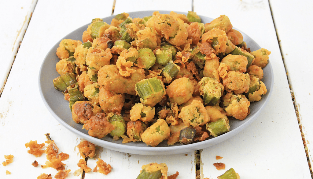 white plate of fried okra on wooden background