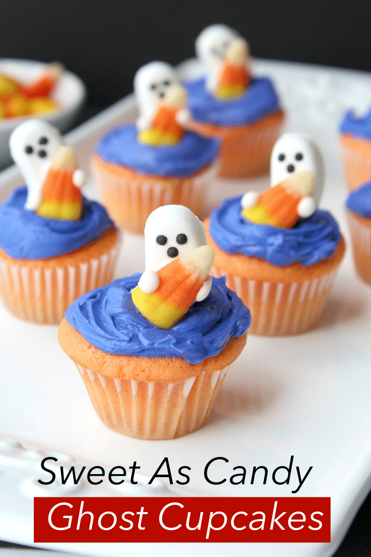 ghost candies on top of blue frosted cupcakes