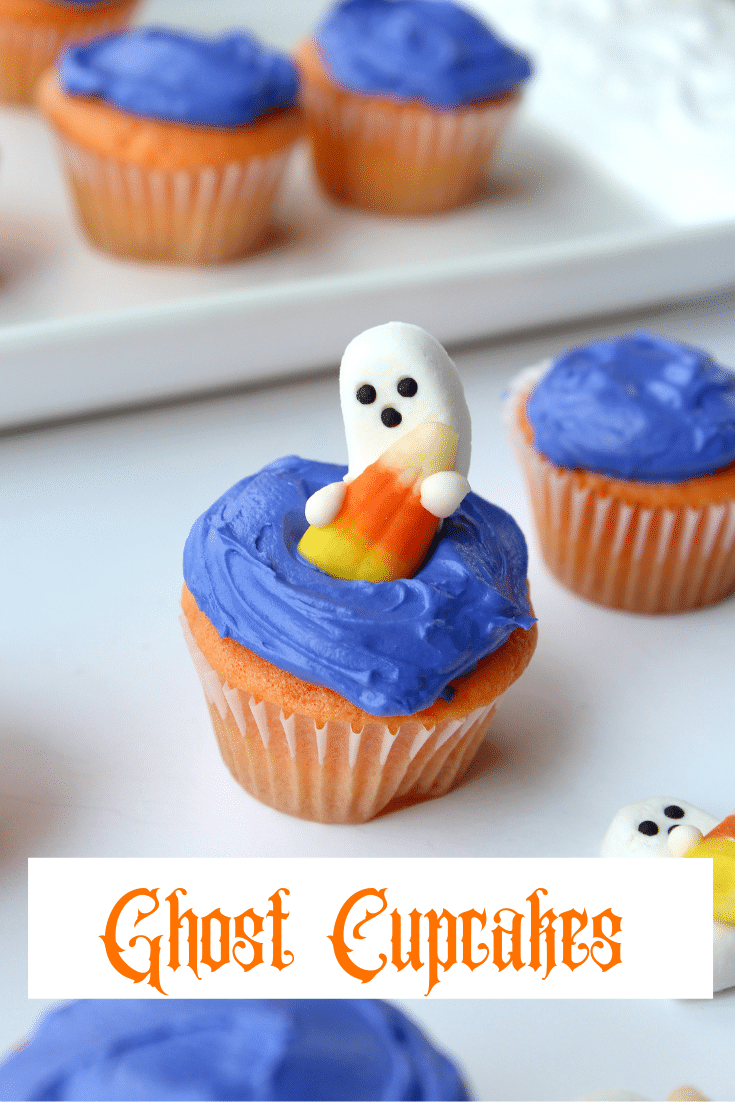 ghost shaped candy on top of blue frosted cupcake