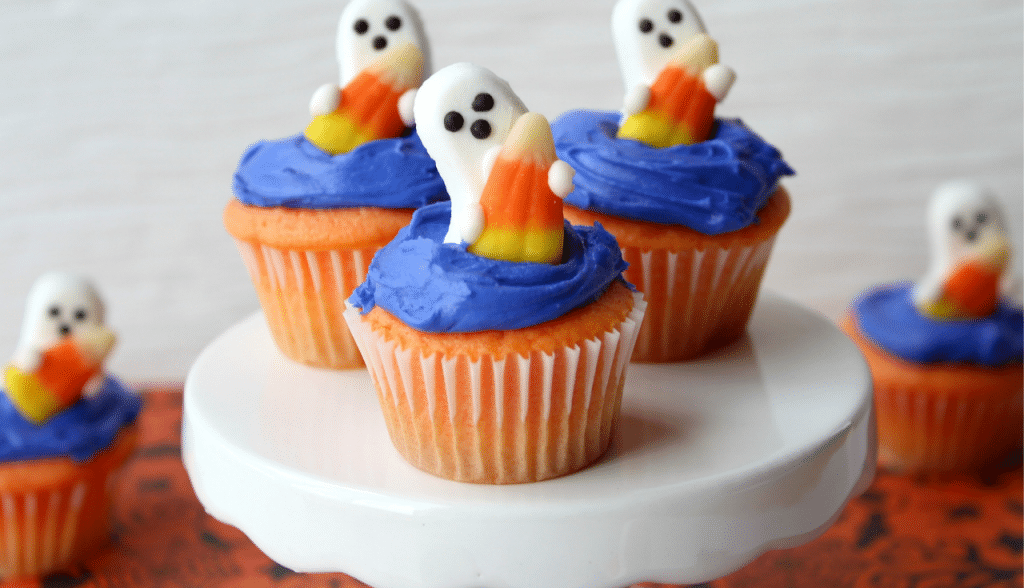 ghost shaped candy on top of blue frosted cupcakes