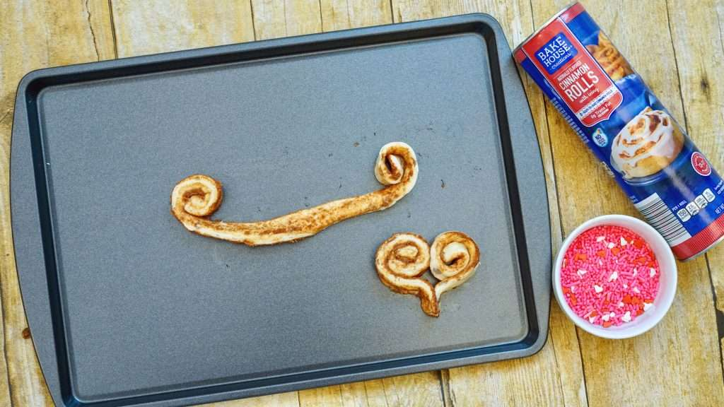 Cinnamon rolls on baking sheet put into heart shape