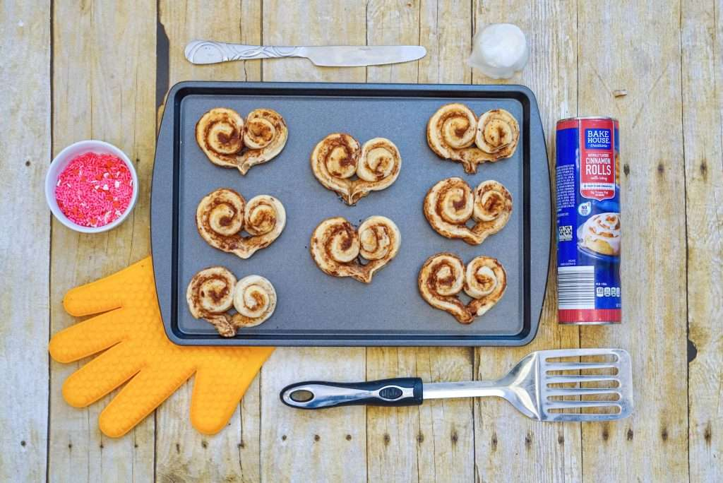 Heart shaped cinnamon rolls ready to bake for Valentine's Day on baking sheet