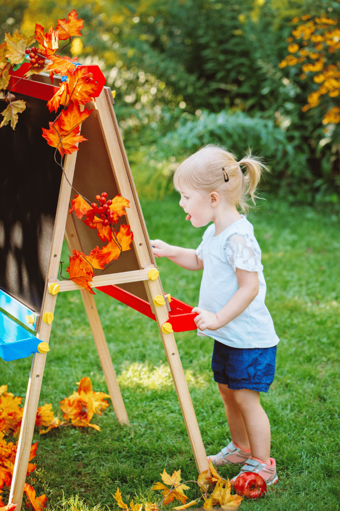 little girl painting at an easel