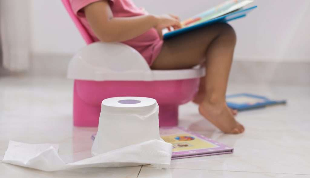 little girl on pink potty chair