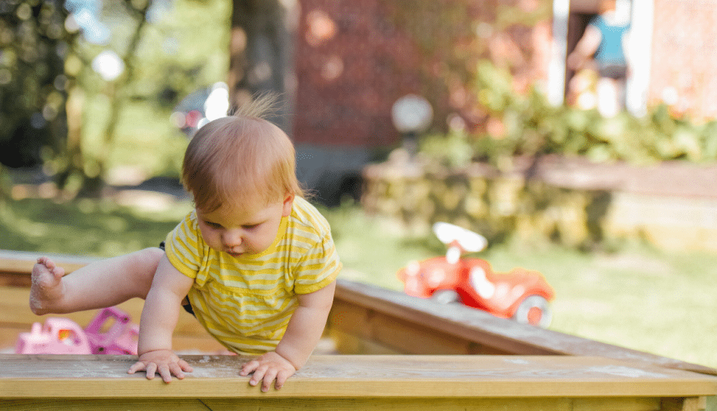 toddler climbing out of sandbox