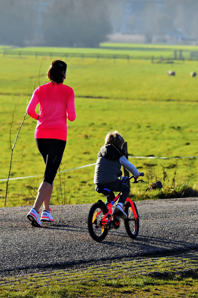 mom jogging next to kid riding his bike.