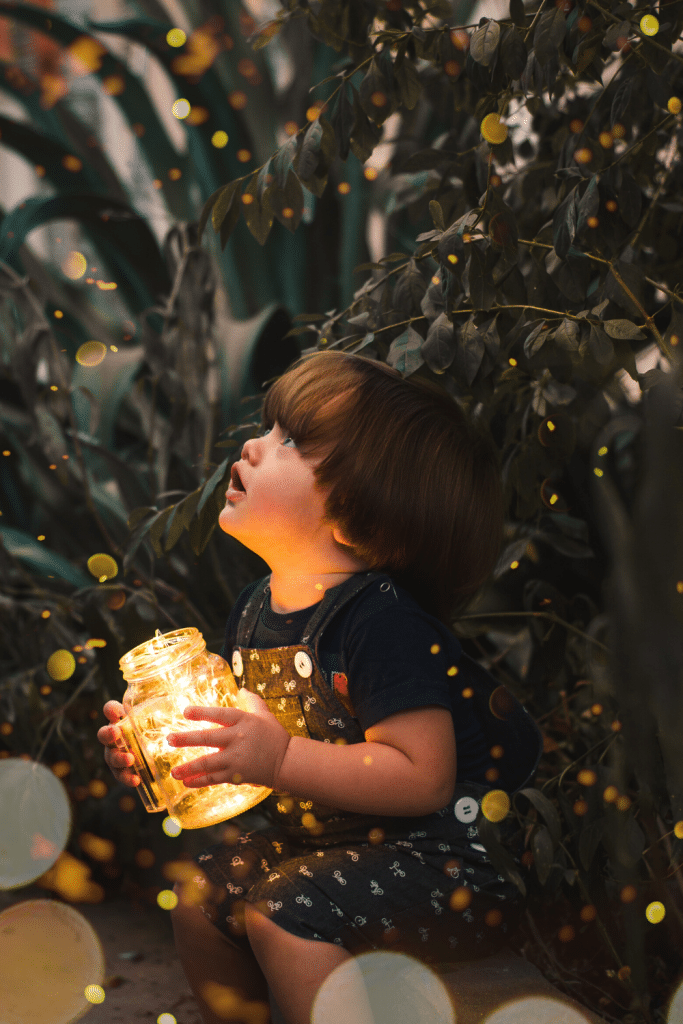 child catching fireflies in jar