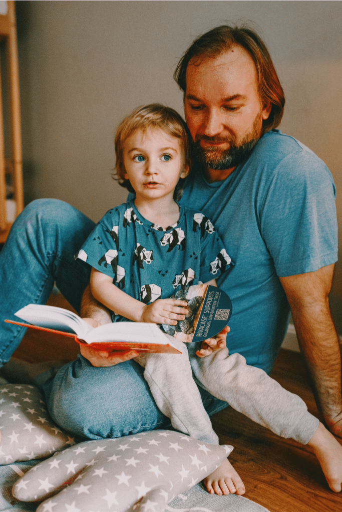 child sitting on dads lap while dad reads to them