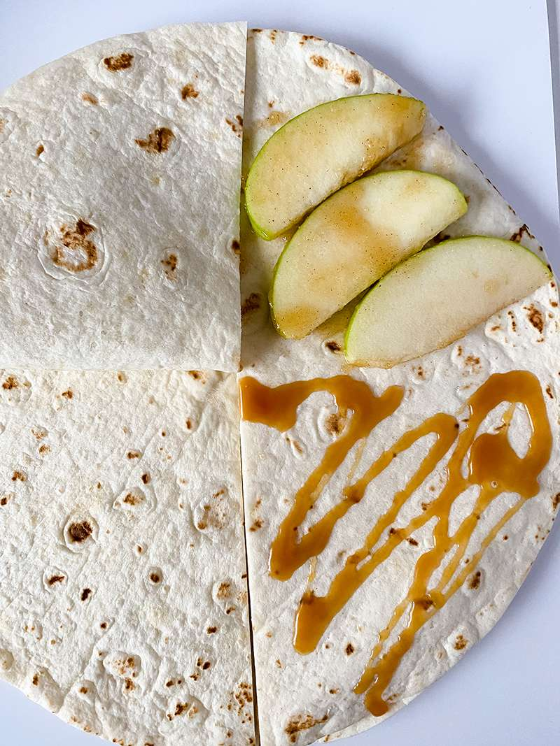 The tortilla being folded over the apple and caramel