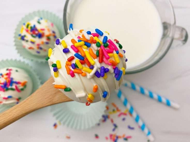 White hot Chocolate Bomb on a spoon with rainbow sprinkles