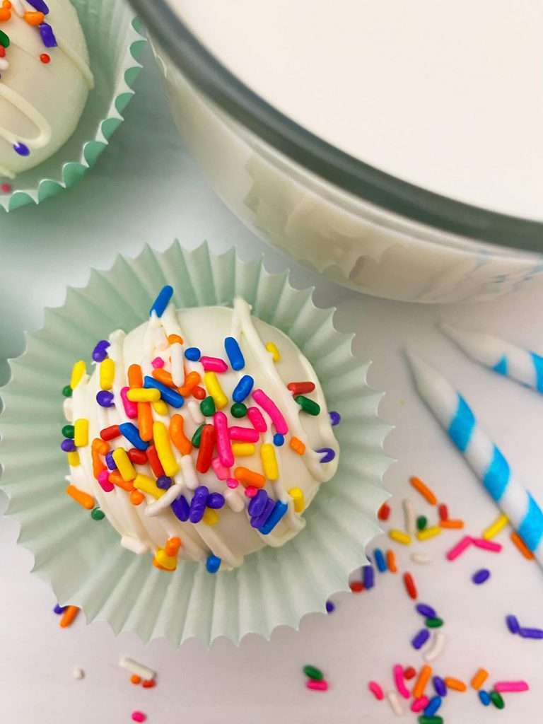 White hot Chocolate Bomb on a spoon with rainbow sprinkles in blue wrapper