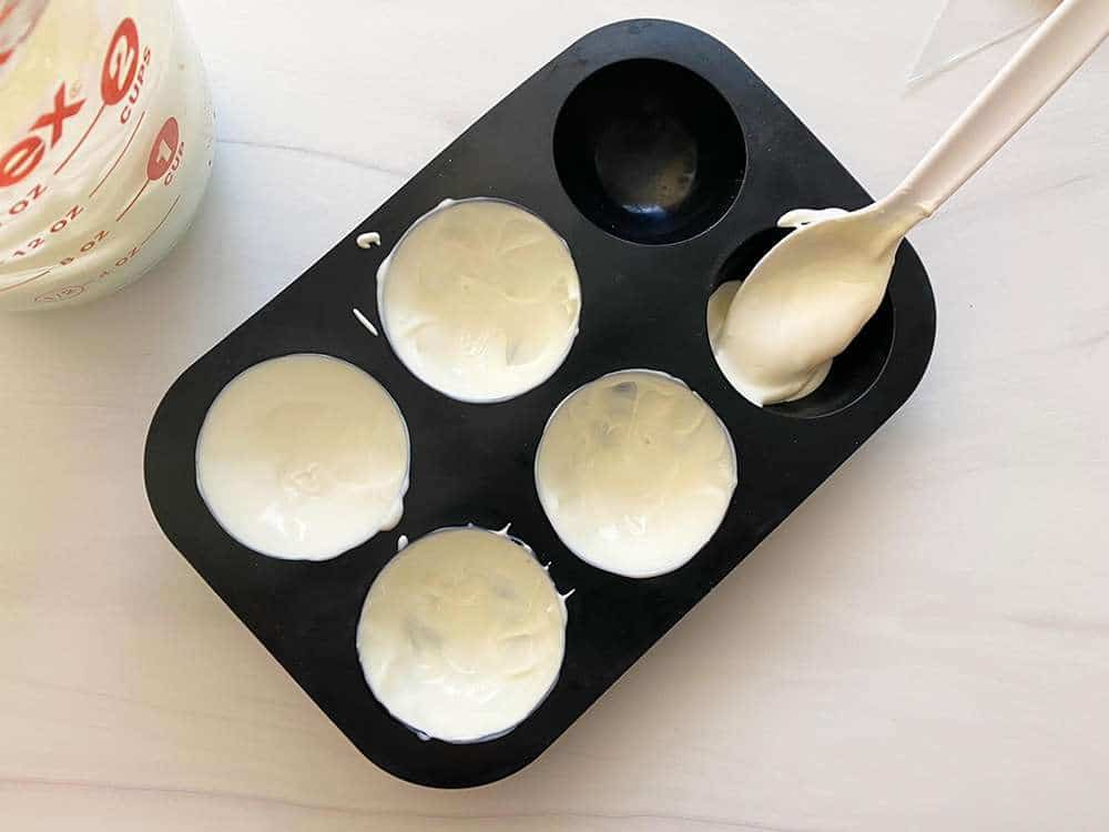 White chocolate being placed into sphere molds